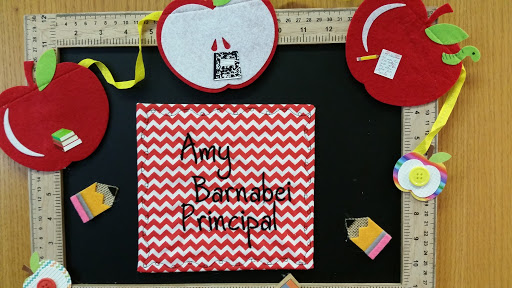 "Sign on wall with words ""Amy Barnabei, Principal"""